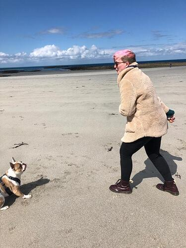 Senior Marketing Executive, Camille Brouard with her dog Bo on the beach in Guernsey